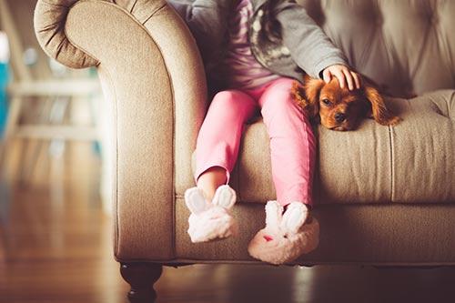 Niña sentada con su perro en sofá tapizado